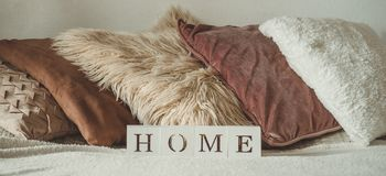 Still life details in home interior of living room and the inscription HOME. A lot of decorative cozy pillows. HOME concept stock photo