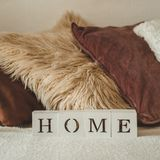 Still life details in home interior of living room and the inscription HOME. A lot of decorative cozy pillows. HOME concept royalty free stock photography