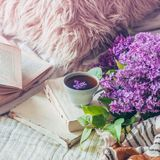 Still life details in home interior of living room. Sweaters and cup of tea with lilac flowers and spring decor on the books stock images