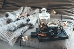 Autumn weekend concept. Still life details of living room. Cup of coffee on rustic wooden tray, candle and warm woolen sweater on sofa, decorated with led lights royalty free stock image