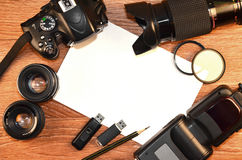 Still life with digital photocamera kit. Complete kit for modern digital SLR camera and blank sheet of paper for copyspace. Cover for online photo accessories Royalty Free Stock Photos