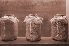 Dry grains in clear glass jars on a shelf with lighting stock photos
