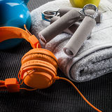 Still-life of earphones, hand grip, towel and kettle bell Royalty Free Stock Photos