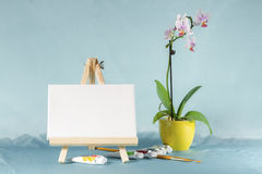 Still life with easel with a blank canvas. Watercolor and  orchid flower Stock Images