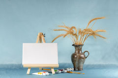 Still life with easel with a blank canvas. Watercolor and wheat ears Stock Photo