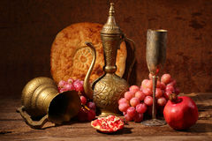 Still-life in east style with grapes, a pomegranate and a jug. Red wine, juicy pomegranate, sweet grapes, flat cake and copper jug Royalty Free Stock Photography