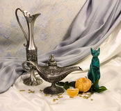 Still-life with east utensils. A figurine and a branch of a tangerine Stock Images