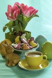 Still life with easter bunny, flowers, cup of coffee, candies and ceramic eggs. Colorful still life with easter bunny, pink flowers, cup of coffee, candies and Royalty Free Stock Images