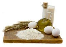 Still-life with eggs. Flour, wheaten ears, olive oil, milk and eggs Royalty Free Stock Photos