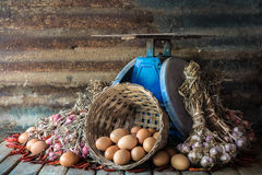 Still life with eggs, onions, garlics, pepper and old blue scales Stock Image