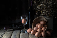 Still life with eggs, wine bottle and dry little flower Stock Photo