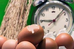 Still life with eggshells and eggs, old broken alarm clock, padd Royalty Free Stock Photos