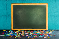 Still life of empty blackboard and colorful paper clips on woode Stock Images