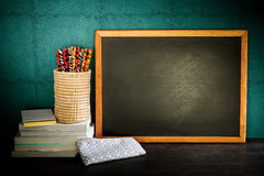Still life of empty blackboard and colorful pencils with books o Stock Images