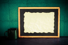 Still life of empty burned paper put on blackboard with coffee c Royalty Free Stock Image
