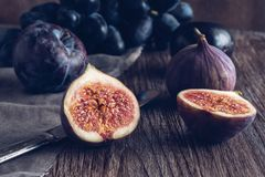 Still life with figs. The fig is cut into halves on a wooden table. Photo toned. Royalty Free Stock Images