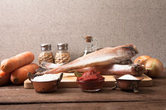 Still life with fish, vegetables and spices on a wooden board Royalty Free Stock Photo