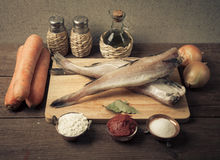 Still life with fish, vegetables and spices on a wooden board. T Stock Image