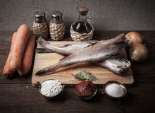 Still life with fish, vegetables and spices on a wooden board. T Stock Photo