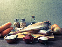 Still life with fish, vegetables and spices on a wooden board. T Stock Photography