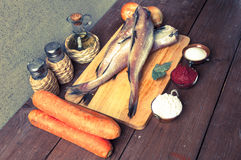 Still life with fish, vegetables and spices on a wooden board. T Royalty Free Stock Photos