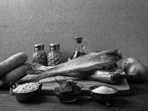 Still life with fish, vegetables and spices on a wooden board. T Royalty Free Stock Photography