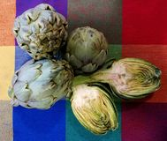 Artichokes on color tablecloth Stock Images
