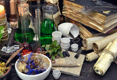 Still life with flasks, magic components, scrolls and books. Old pharmacy, esoteric or alternative medicine concept. Black magic and occult objects, medieval Royalty Free Stock Photo
