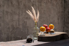 Still life with flower foxtail weed in glass bottles and fruits Stock Photography