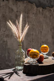 Still life with flower foxtail weed in glass bottles and fruits Stock Photos