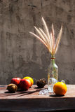 Still life with flower foxtail weed in glass bottles and fruits Stock Photo
