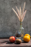 Still life with flower foxtail weed in glass bottles and fruits Stock Image