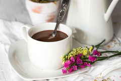 Still life of flowers in jar and cup with spoon Stock Images