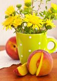 Still life with flowers and peach. Es Stock Photography