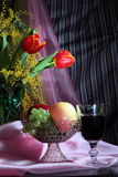 Still life with flowers, red wine and fruits Stock Images