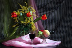 Still life with flowers, red wine and fruits Stock Photos