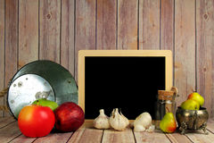 A still life of food. A still life of apples,garlic,fruits and vegetables with a slate with copy space Royalty Free Stock Photos