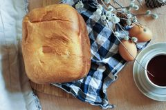 Still life of food. The top view of the homemade bread lying on a checkered napkin and a cup of coffee, eggs and  a willow branch from above Royalty Free Stock Images