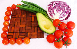 Still life frame from wooden cutting board, cherry tomatoes and. Greens, avocado and red cabbage Stock Photo