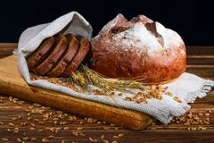 Still-life with fresh bread on sackcloth on black background Stock Image