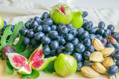 Still life of fresh colorful fruits. Bunch of black grapes, gree Stock Photos