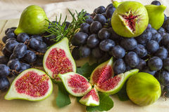 Still life of fresh colorful fruits. Bunch of black grapes, gree Stock Images