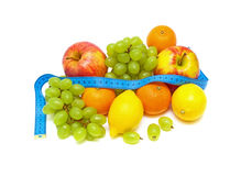 Still Life. fresh fruit and measuring tape. Still Life. fresh fruits and a measuring tape on white background Royalty Free Stock Photography