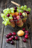 Still life with fresh fruits in wicker basket on wooden table Royalty Free Stock Photos