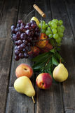 Still life with fresh fruits in wicker basket on wooden table Stock Photography