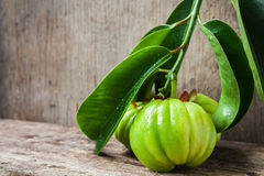 Still life with fresh garcinia cambogia on wooden background Stock Photos