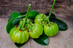 Still life with fresh garcinia cambogia on wooden background (Th Stock Photo