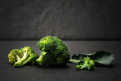 Still life with fresh green broccoli on black stone plate Royalty Free Stock Image