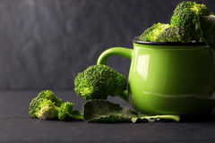 still life with fresh green broccoli in ceramic cup on black stone plate royalty free stock photography