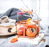 Still life fresh persimmon. In a basket on a serving table preparation for breakfast concept of holding Stock Photo
